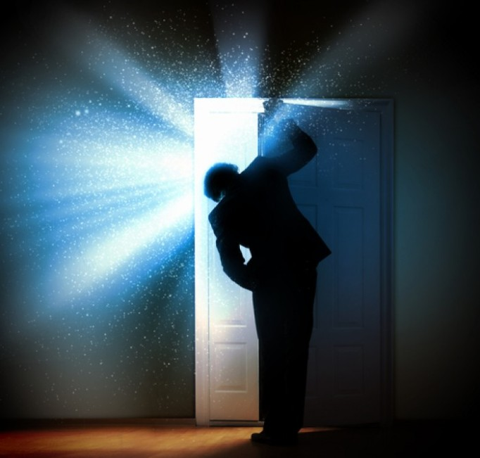 man-opening-door-to-bright-light